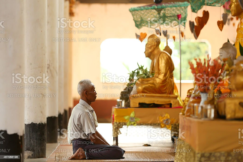 Man praying in front of golden Buddhas. stock photo