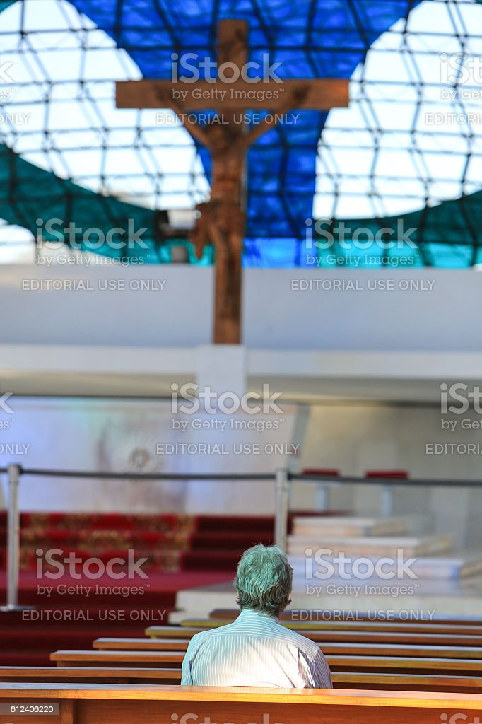 Man praying inside the Cathedral of Brasilia stock photo