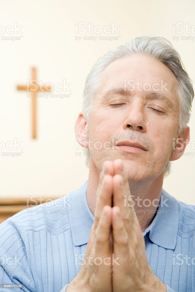 Man praying with rosary beads stock photo