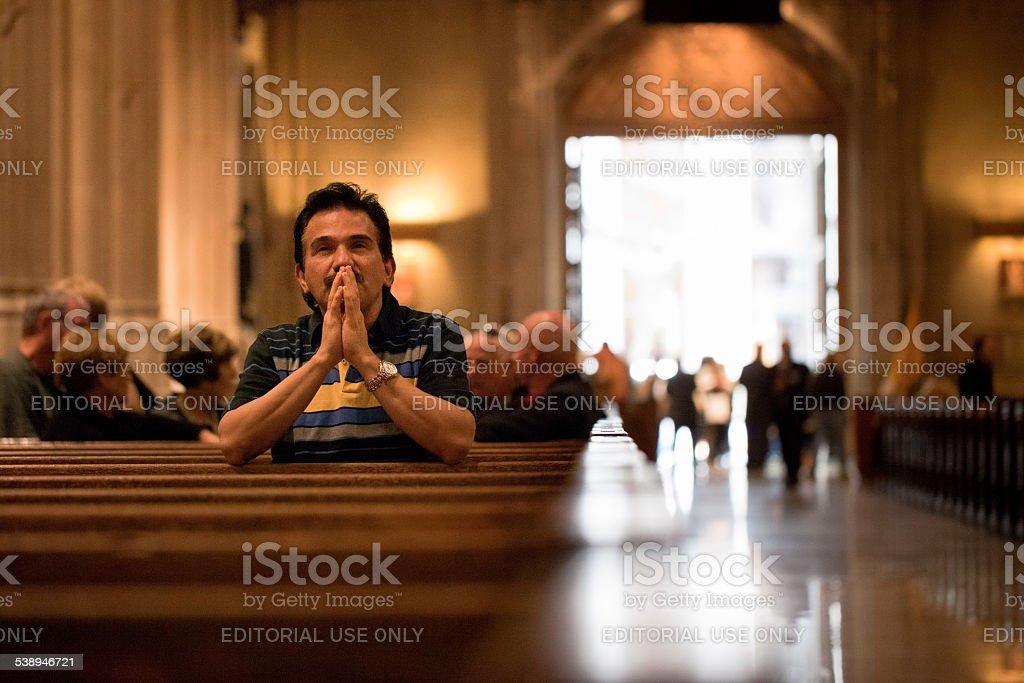 Man prays at St Patrick's Cathedral stock photo