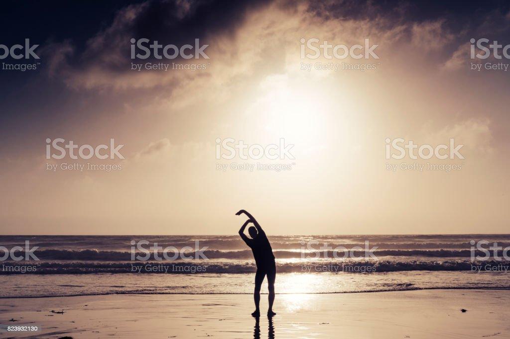 Man Pre run stretching near sunset on the beach. stock photo