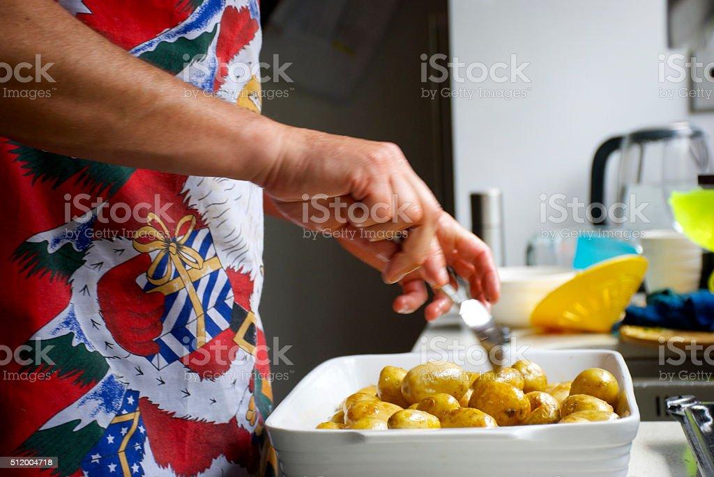 Man prepares the new potatoes for Christmas Dinner stock photo