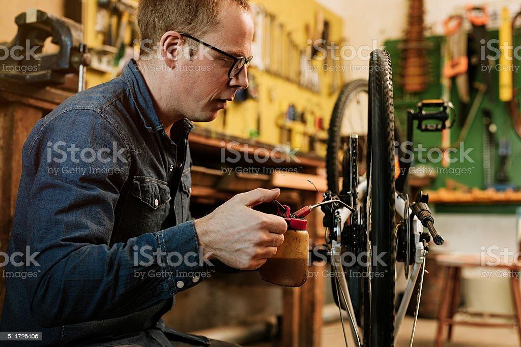 Man preparing bicycle for spring in his garage stock photo