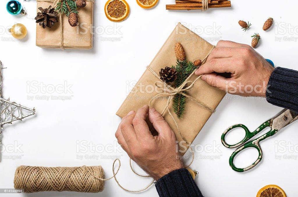 Man preparing Christmas gift on a white background stock photo