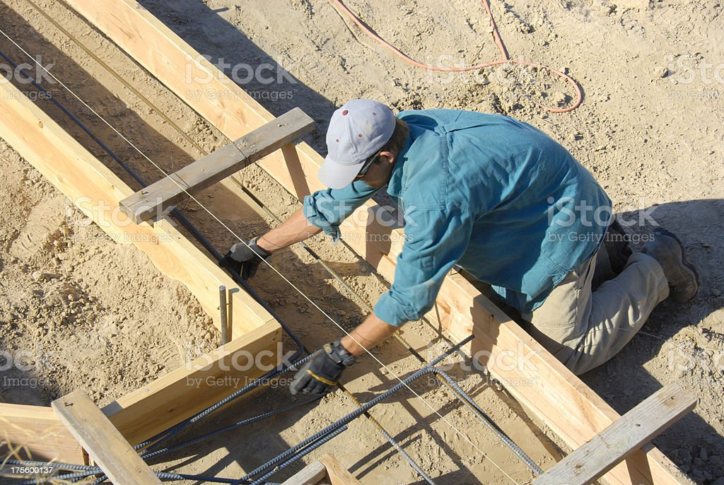 Man preparing footings for cement during home construction stock photo
