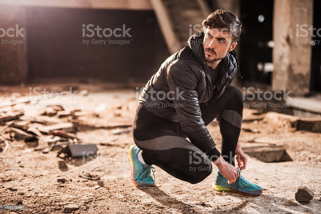 Man preparing for exercising in ruin and tying his shoelaces. stock photo