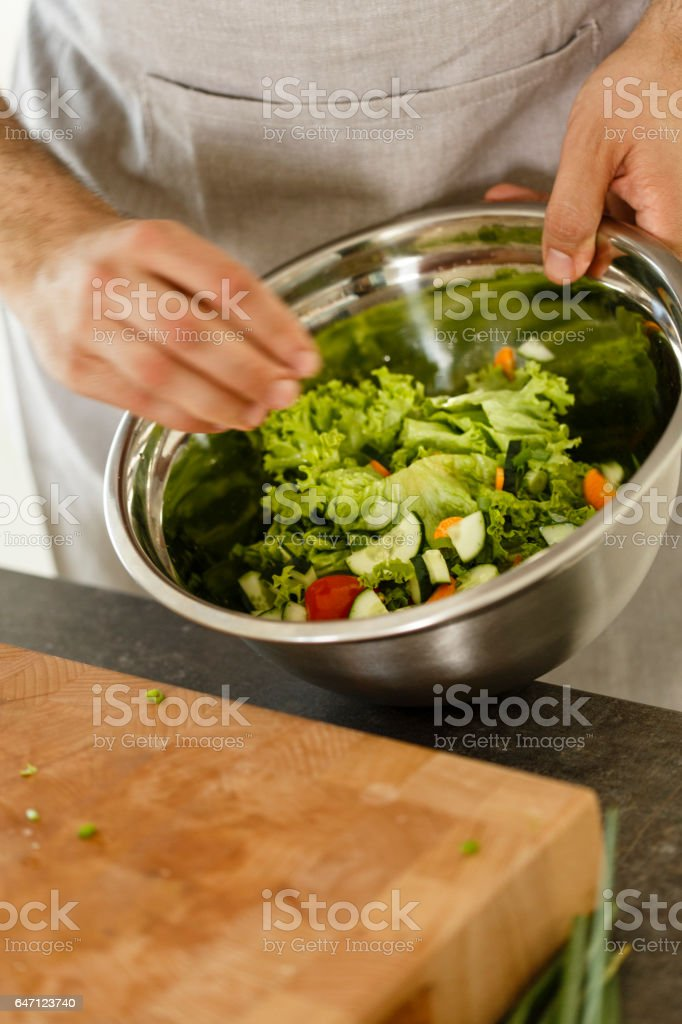 Man preparing fresh vegetable salad stock photo