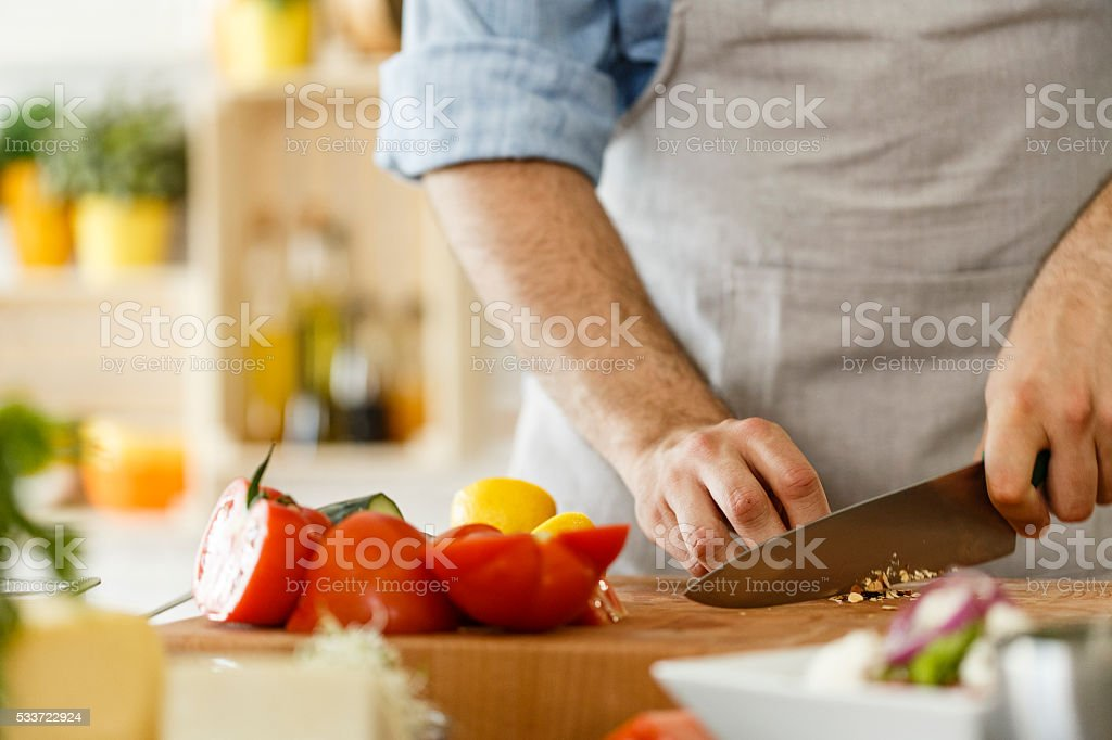 Man preparing healthy vegetables salad, cutting almond stock photo