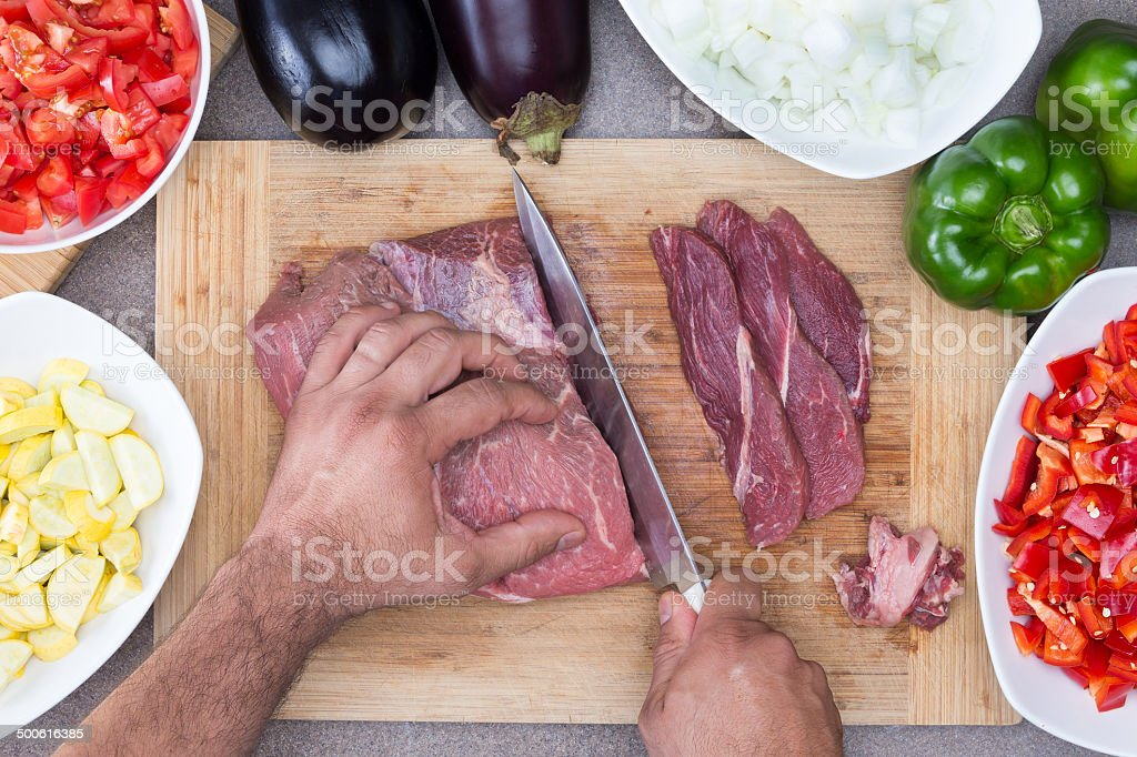 Man preparing meat and vegetables in a kitchen stock photo