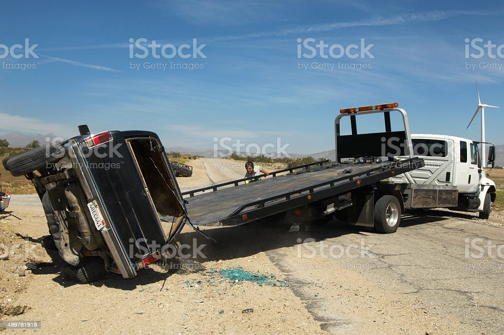 Man preparing to lift crashed car onto tow truck stock photo