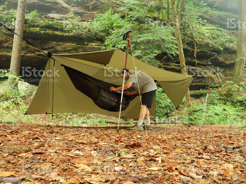 Man preparting modern camping hammock in campsite stock photo