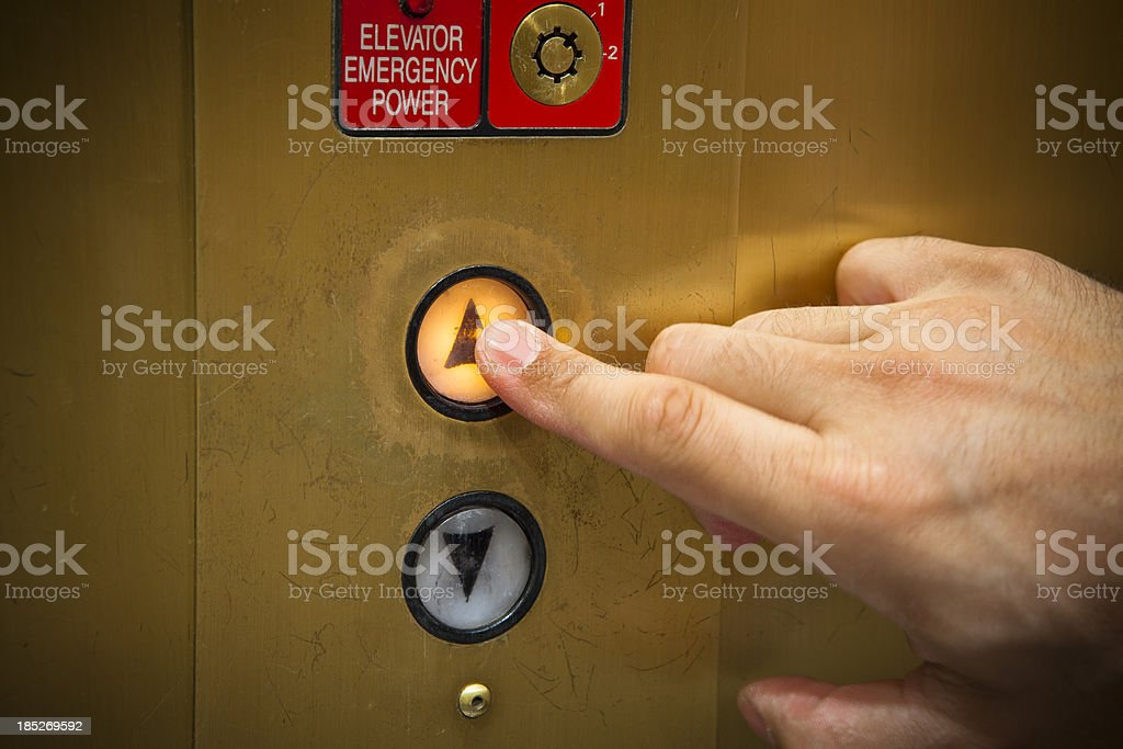 Man pressing illuminated lift button close-up royalty-free stock photo