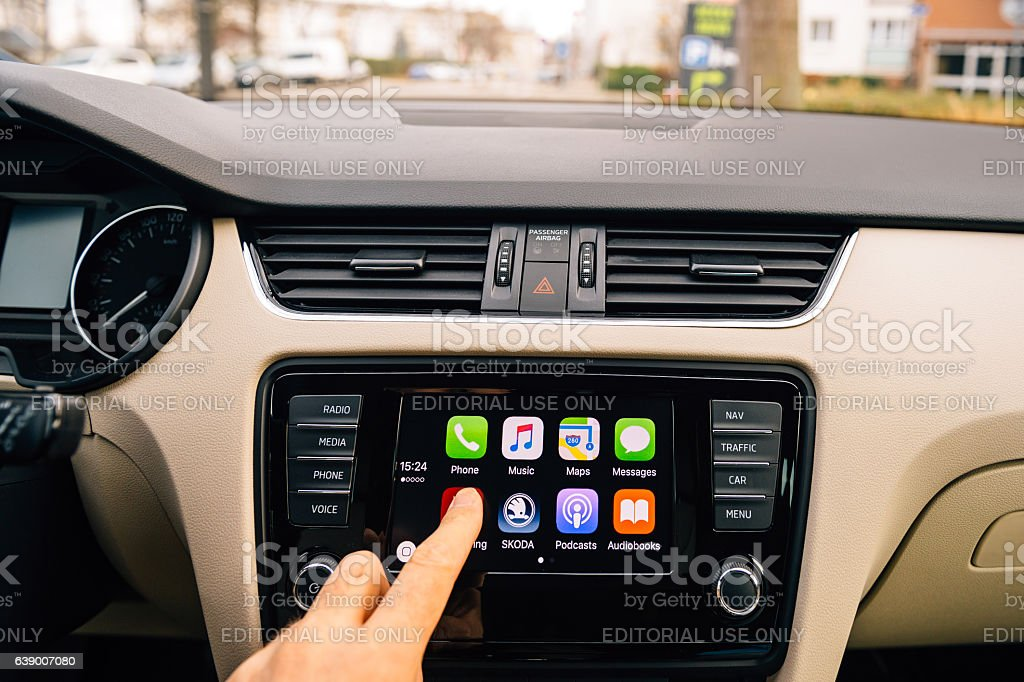 Man pressing Now Playing button on the Apple CarPlay stock photo