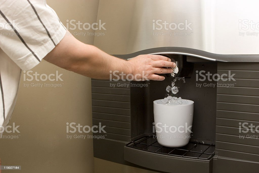 A man pressing the button of an ice machine over a white tub stock photo