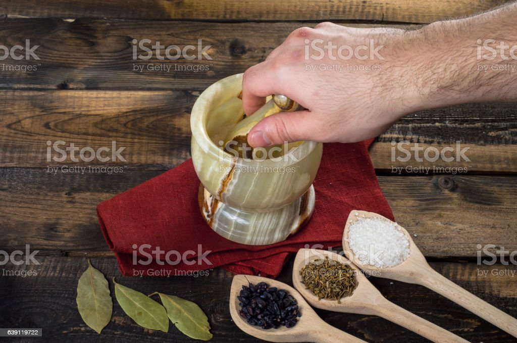 man prevents the spices in a mortar stock photo