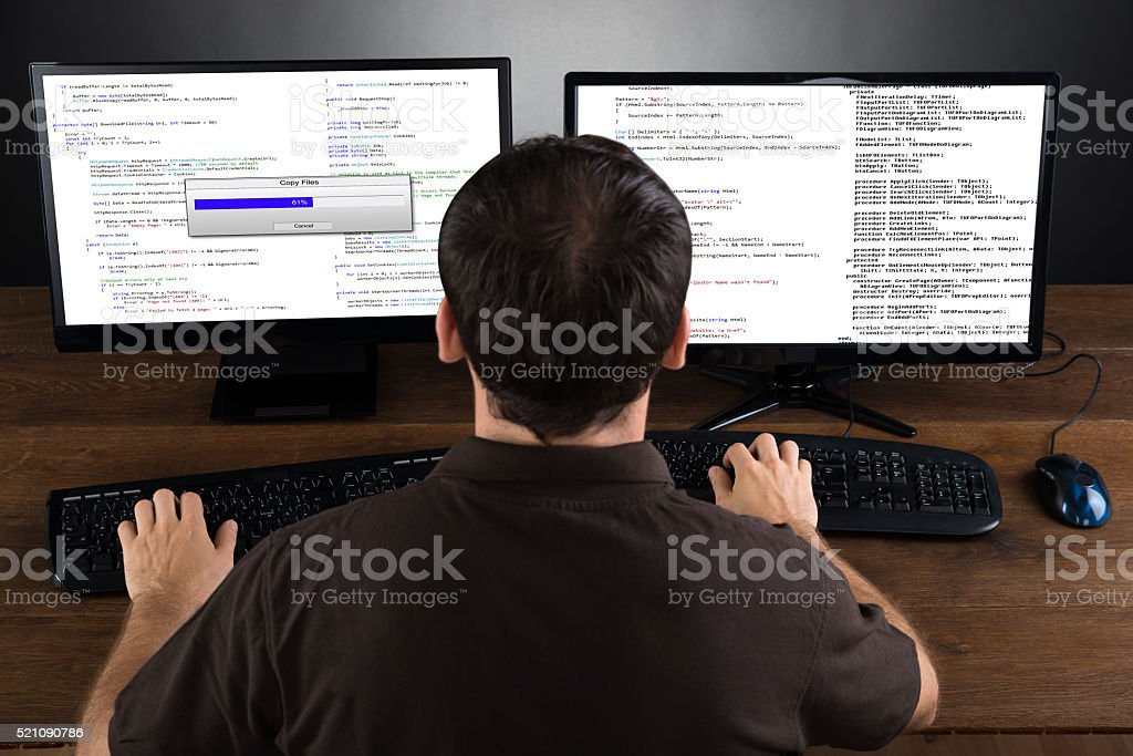 Man Programming Code On Computers stock photo
