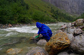 man prospector panning gold on river with sluice box