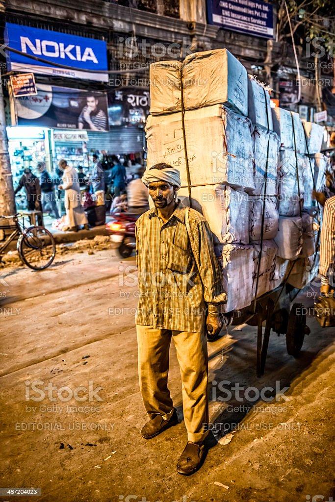 Man pulling a heavy load at Old Delhi market stock photo