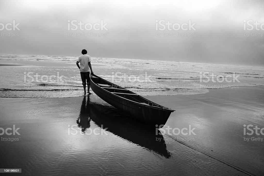 Man Pulling Canoe Boat Off Beach into Water stock photo