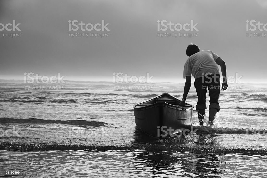Man Pulling Canoe into Water, Black and White royalty-free stock photo
