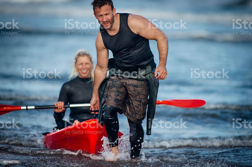 Man Pulling Girl in Kayak out of the sea stock photo