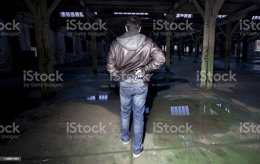 Man pulling gun from secret place on his waist stock photo