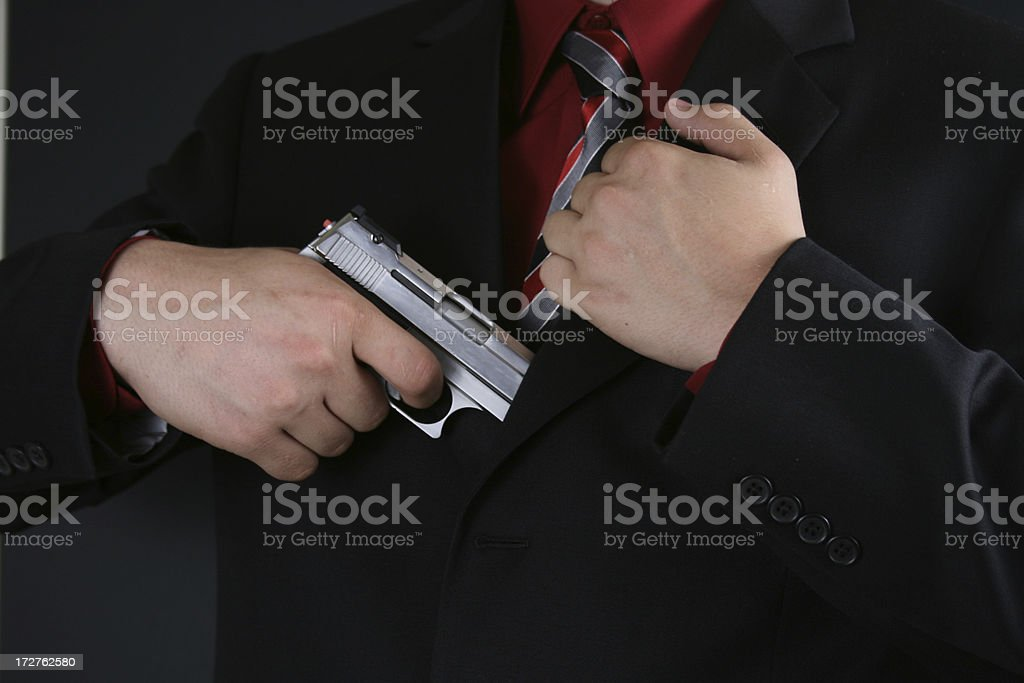 Man Pulling Gun out of Suit royalty-free stock photo
