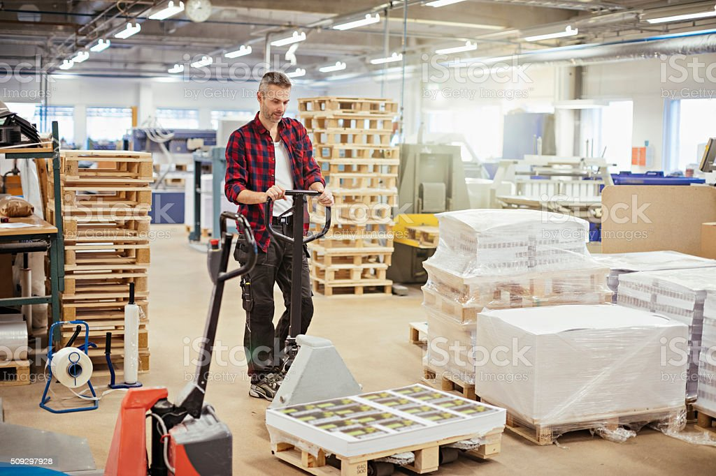 Man pulling hand truck stock photo