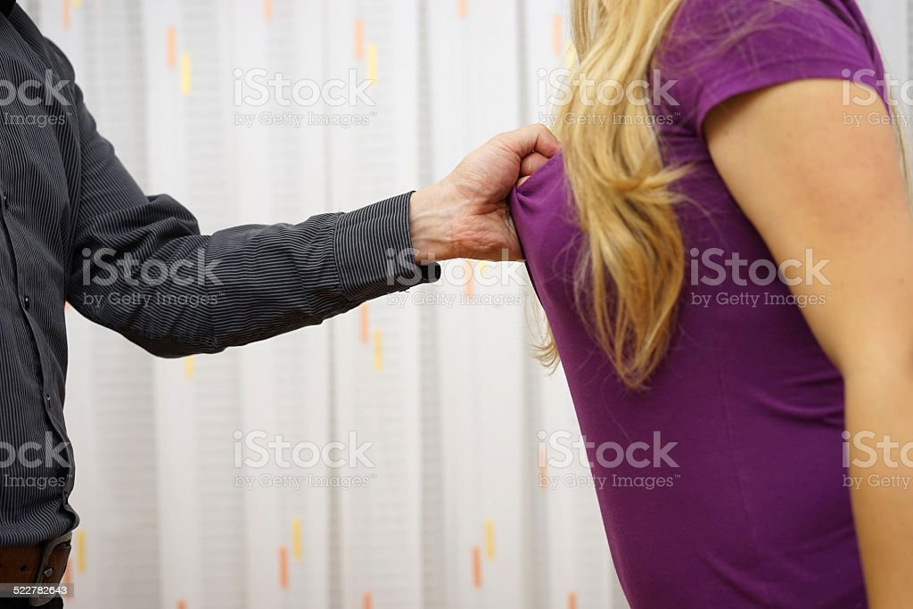 man  pulling his girlfriend's shirt, violence concept over woman stock photo