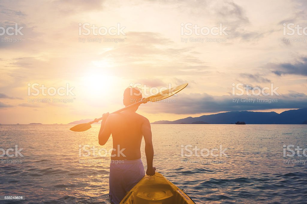 Man pulling kayak to the sea in sunset stock photo