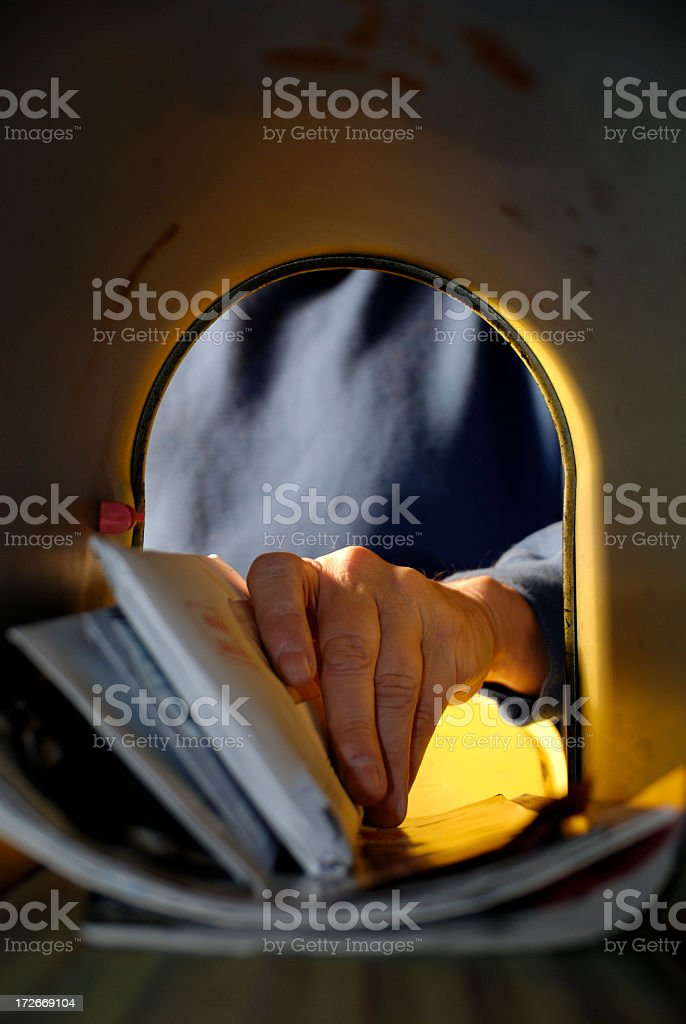 A man pulling mail out of a mailbox stock photo