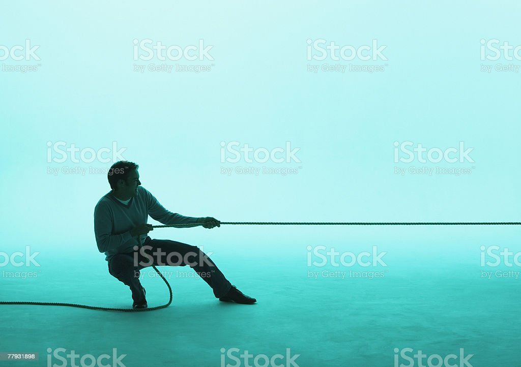 Man pulling on a rope stock photo