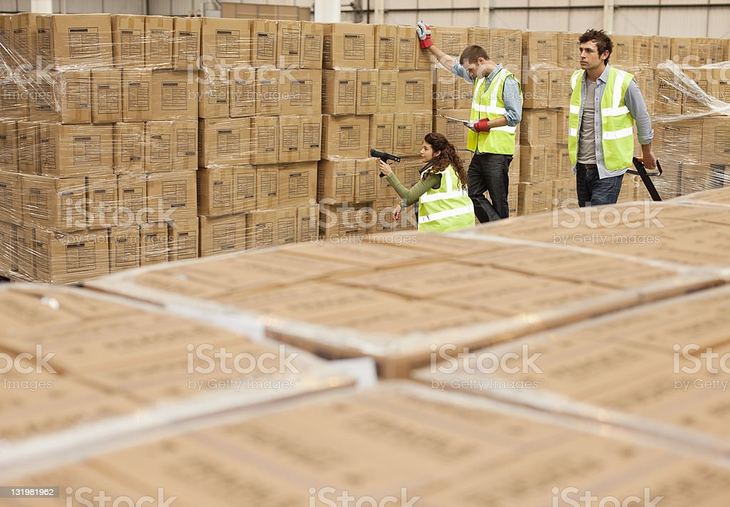 Man pulling push cart by workers taking inventory in warehouse stock photo