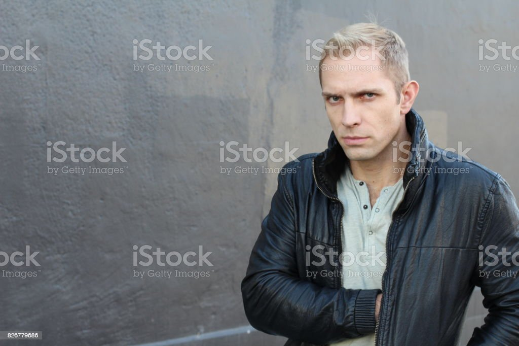 Man pulling something out of his jacket stock photo