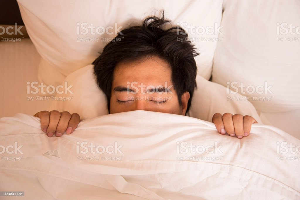 Man pulls covers up in comfortable hotel room bed.  Sleeping. stock photo