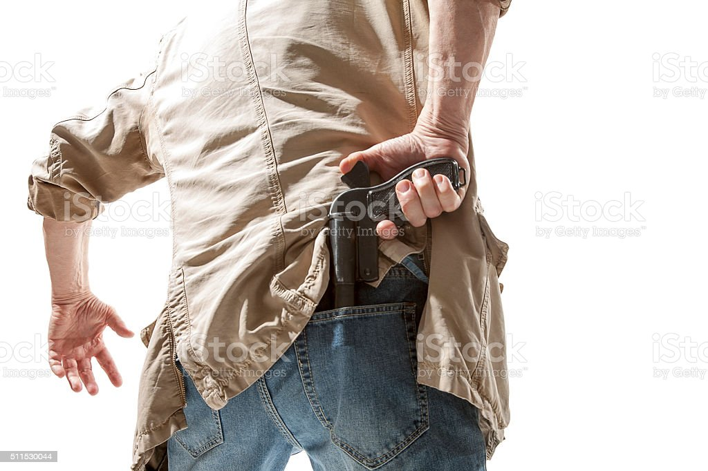 Man pulls out a gun from his back stock photo