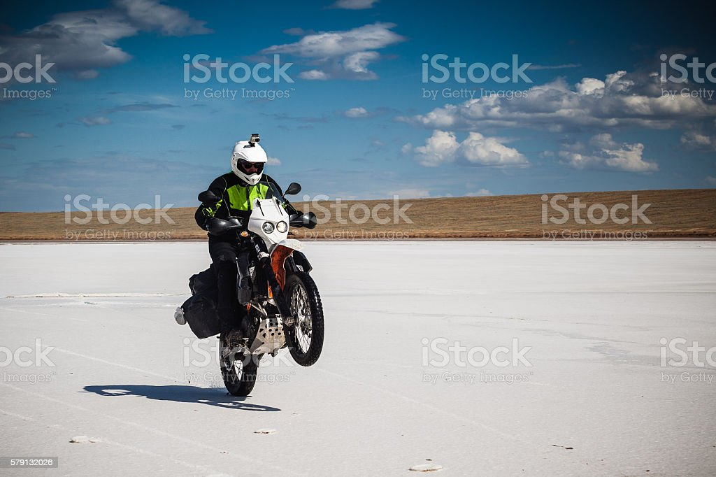 Man pulls wheelie by motorbike on salt pan. stock photo