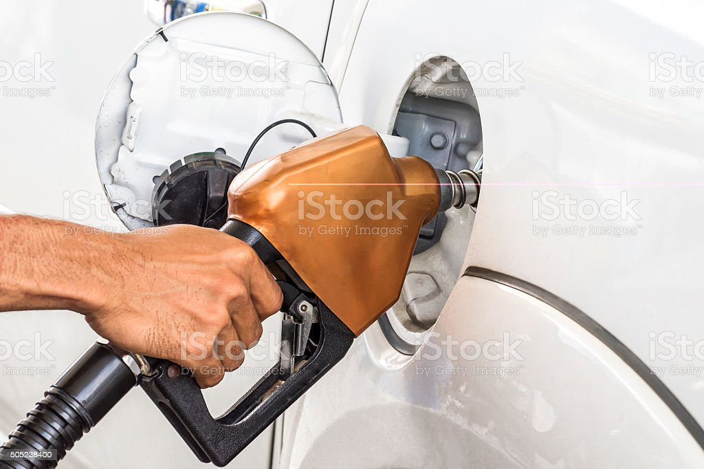 man pumping gasoline fuel in car at gas station stock photo