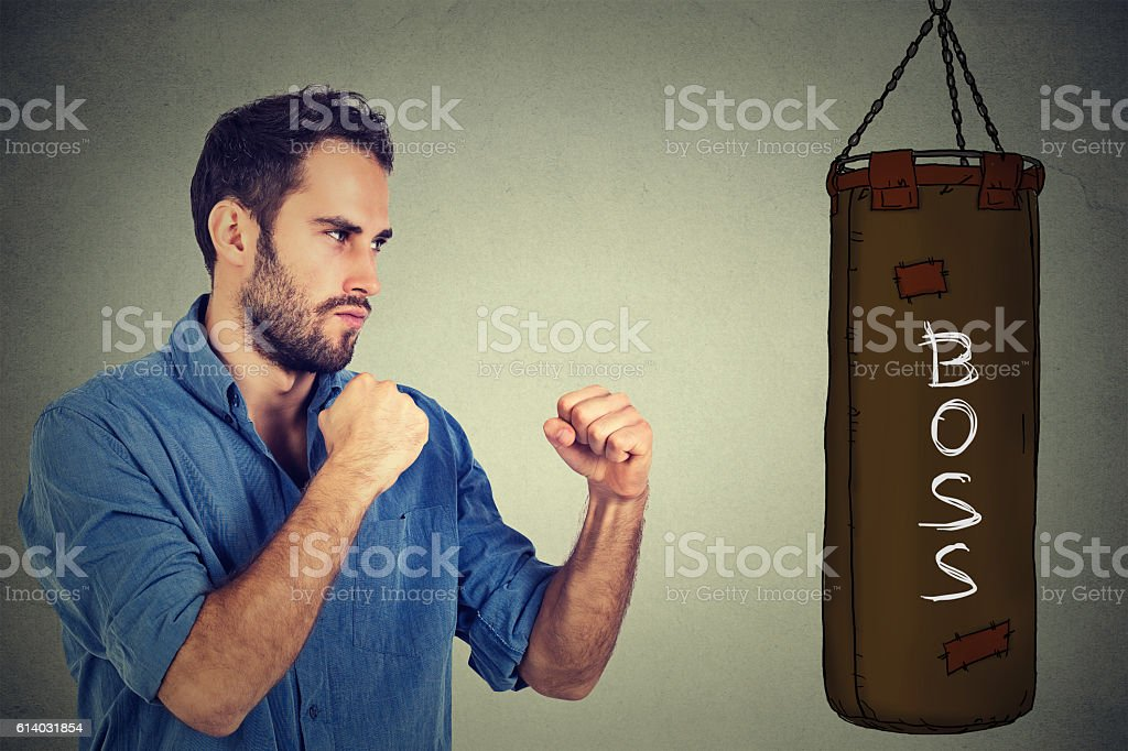man punching boxing bag with boss written on it stock photo