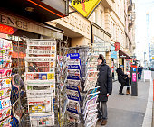 Man purchases a International press newspapers from a newsstand