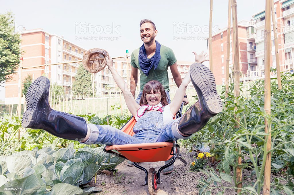 man pushes his girlfriend in wheelbarrow in the garden stock photo