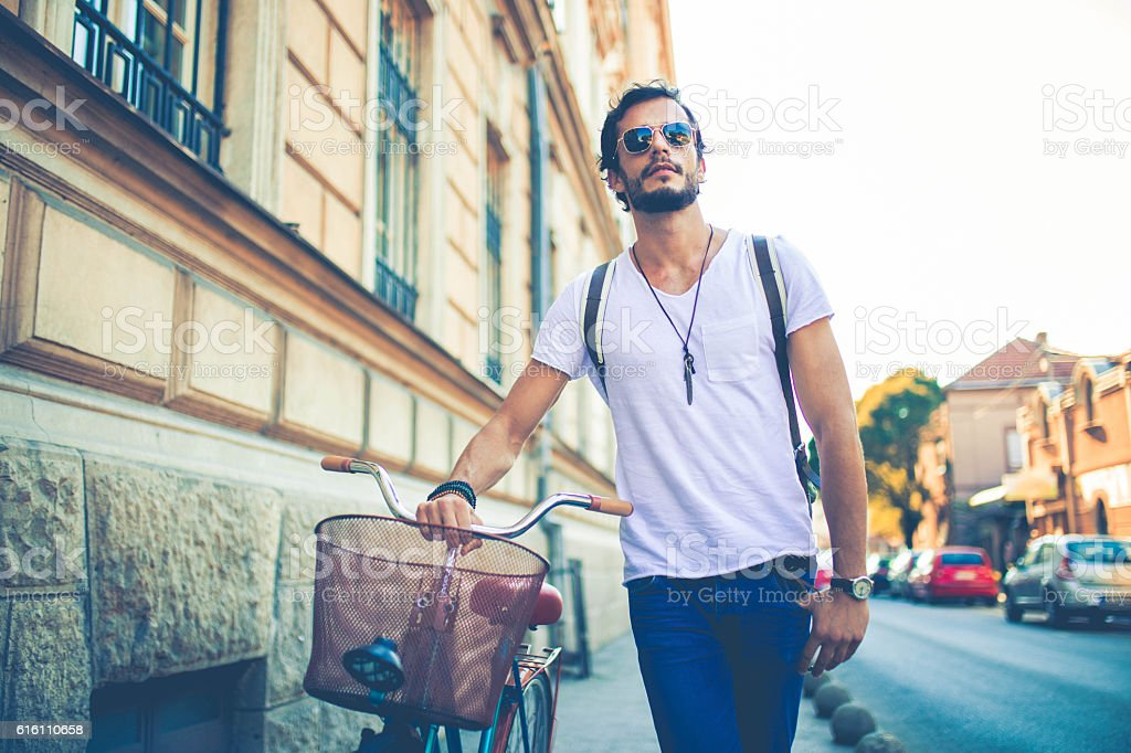 Man pushing a bike stock photo