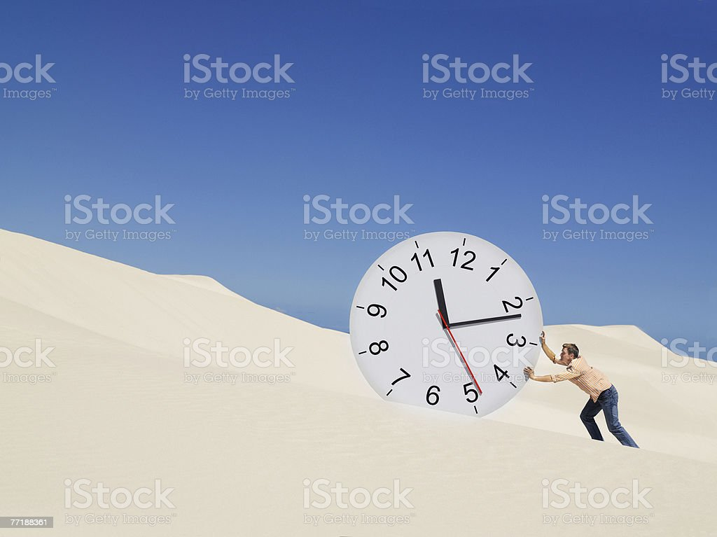 A man pushing a clock in the desert royalty-free stock photo