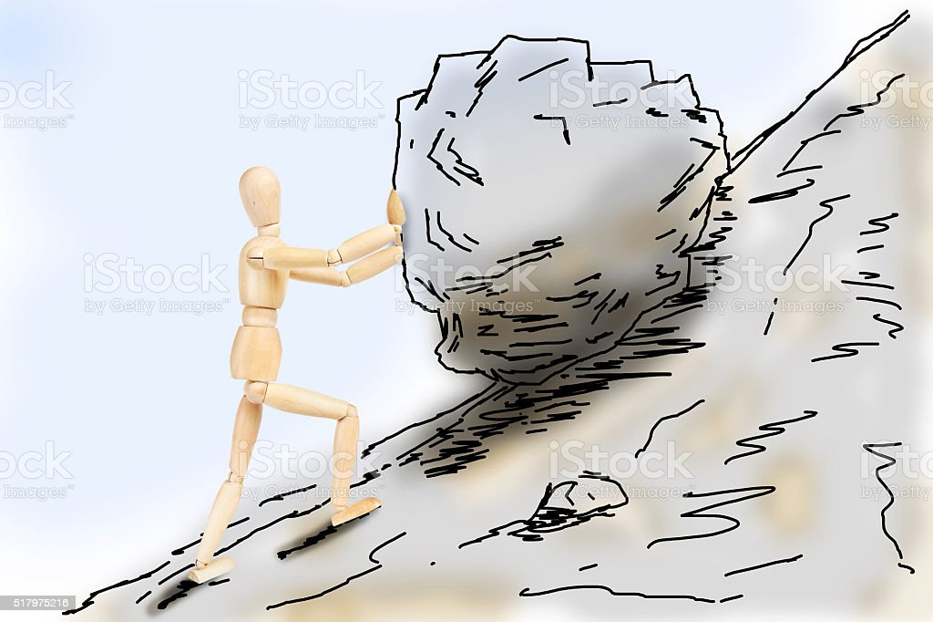 Man pushing a stone up to the mountain slope stock photo