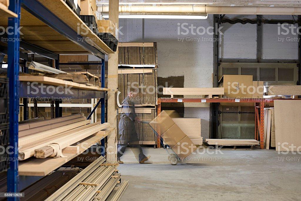 Man pushing boxes in warehouse stock photo