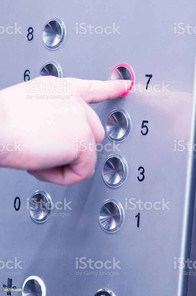 man pushing buttons on an elevator stock photo