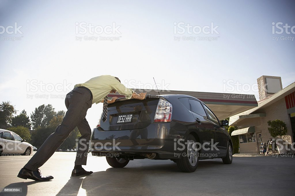 Man pushing car into service station stock photo