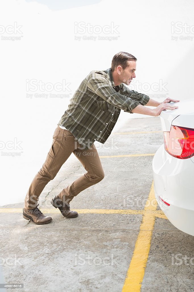 Man pushing his broken down car stock photo