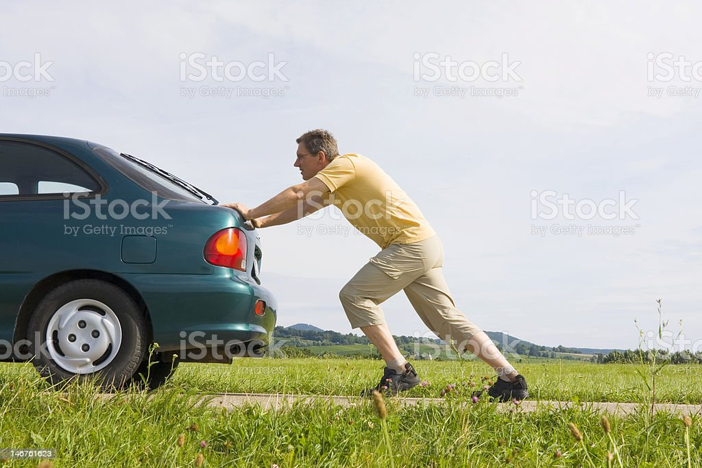 Man pushing his car stock photo