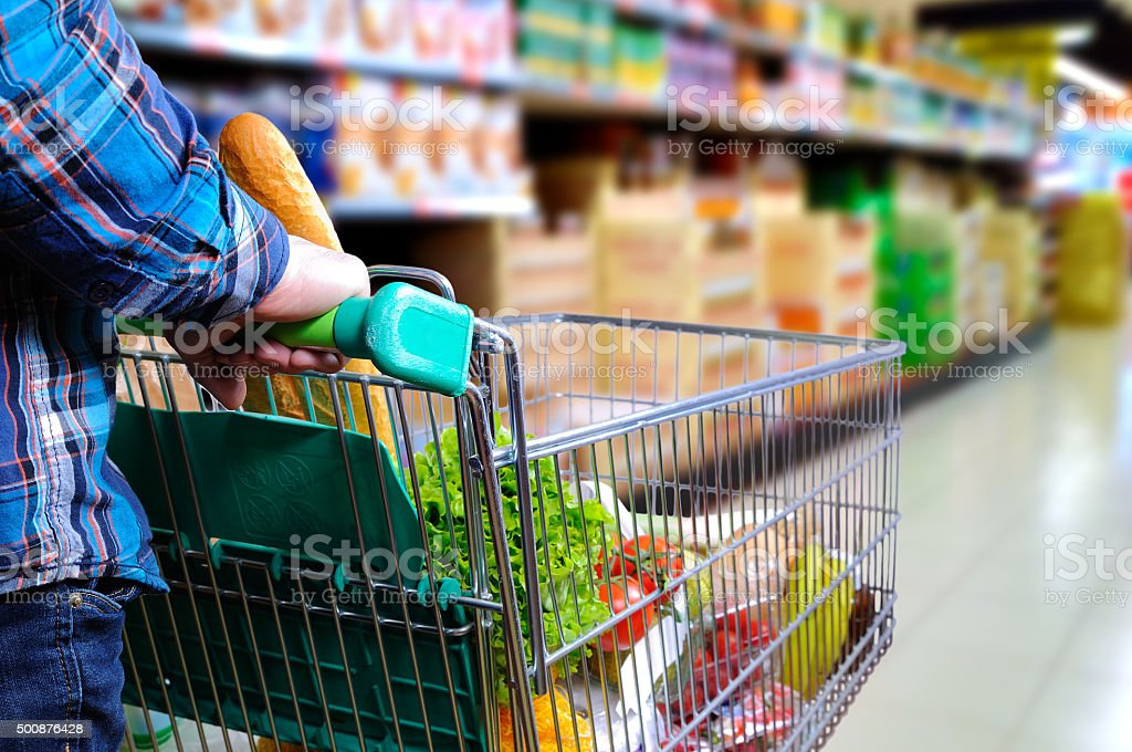 Man pushing shopping cart in the supermarket aisle stock photo